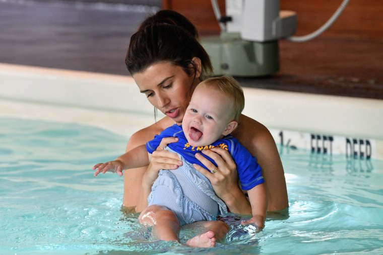 Here's how I would normally hold my baby in the pool. While she may be smiling, notice how most of her body is out of the water?