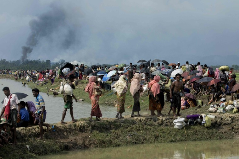 Image: Smoke billows above what is believed to be a burning village in Myanmar's Rakhine state as members of the Rohingya Muslim minority take shelter