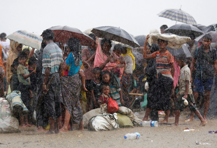 Image: Rohingya refugees stand in an open area during heavy rain as they are held by the Border Guard Bangladesh (BGB) after crossing the border, in Teknaf