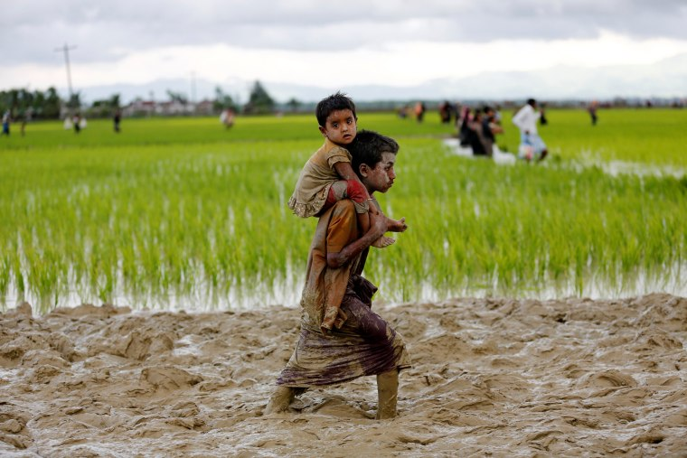 Image: A Rohingya boy carries a child while walking in the mud after crossing the Bangladesh-Myanmar border in Teknaf