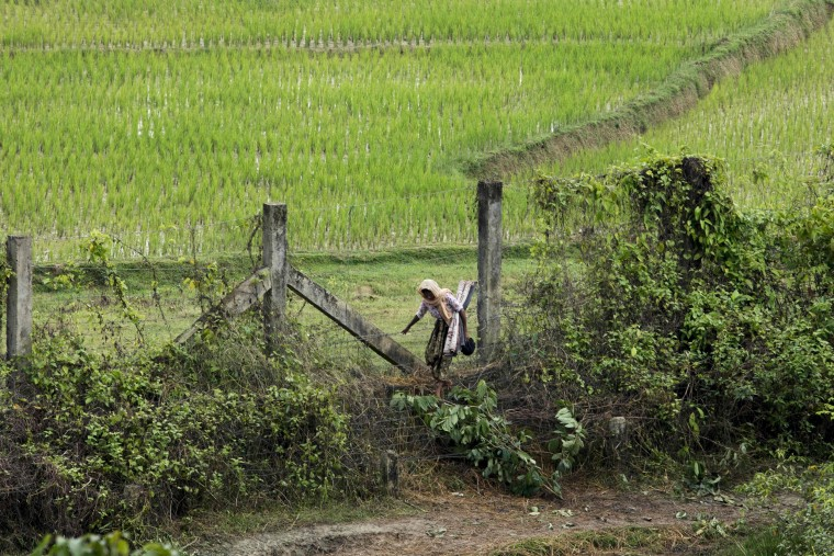 Image: A Rohingya woman crosses a barbed-wire fence near Ukhia, near the border between Bangladesh and Myanmar