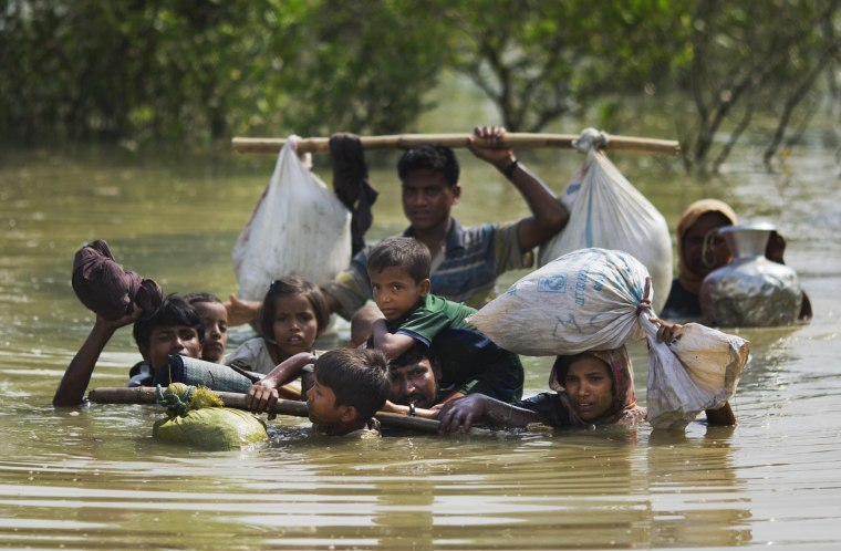 Image: A Rohingya family reaches the Bangladesh border after crossing a creek of the Naf river
