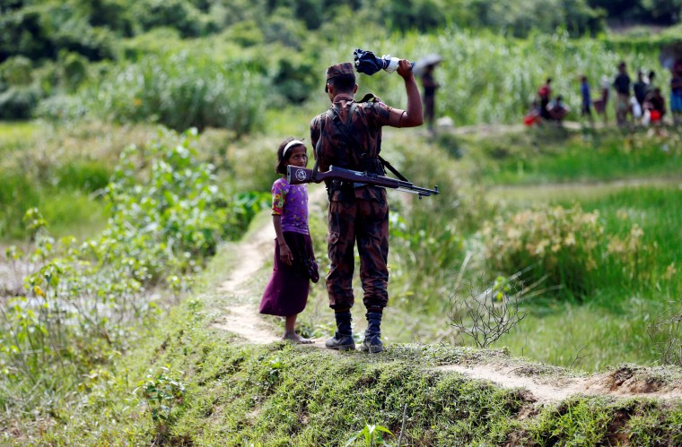 Image: A member of Border Guard Bangladesh (BGB) tells a Rohingya girl not to come on Bangladesh side, in Cox's Bazar