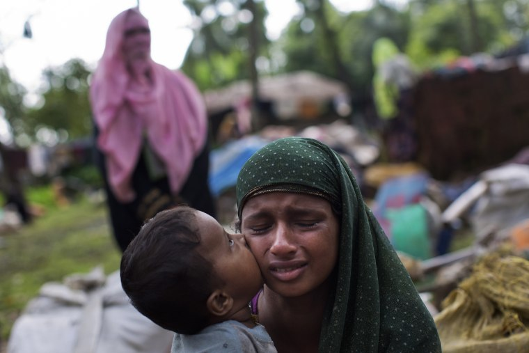 Image: A Rohingya Muslim kisses his mother as they rest after having crossed over from Myanma
