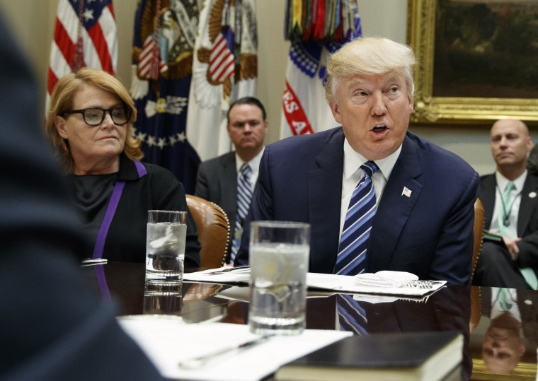 Image: President Donald Trump, seated next to Sen. Heidi Heitkamp, D-N.D.