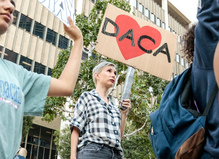 Image: Allison Agsten of Los Angeles stands with supporters of the Deferred Action for Childhood Arrivals (DACA) program during a rally outside the Edward R. Roybal Federal Building in Los Angeles, California