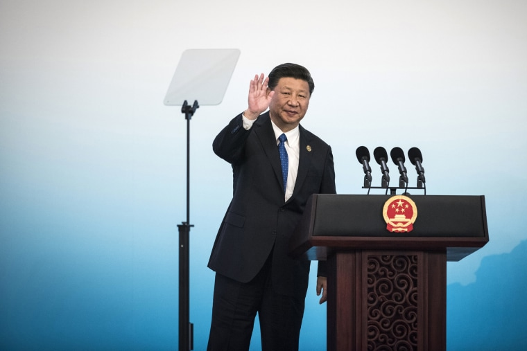 Image: China's President Xi Jinping waves during a press conference