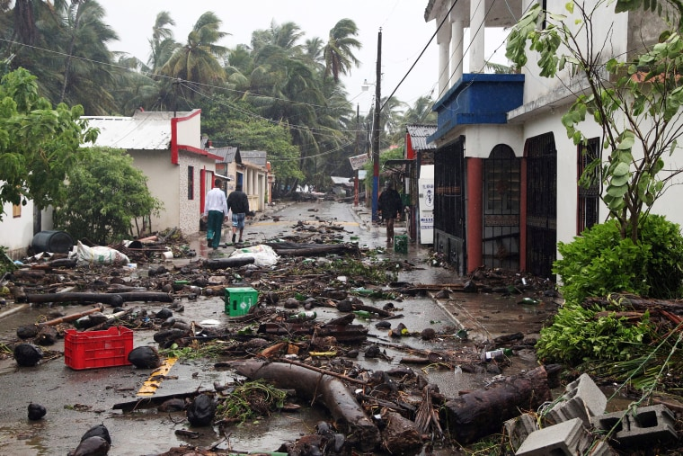 Image: People walk on a street covered in debris as Hurricane Irma moves off from the northern coast of the Dominican Republic, in Nagua