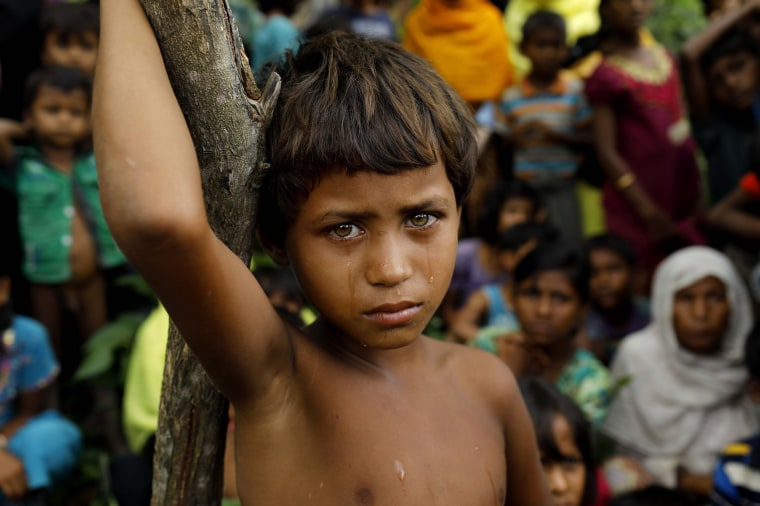 Image: A Rohingya refugee girl looks next to newly arrived refugees