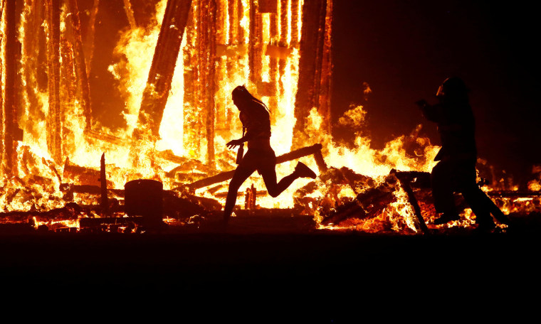 "Image: Burning Man participant runs into the flames of the ""Man Burn"" at the Burning Man arts and music festival in the Black Rock Desert of Nevada"