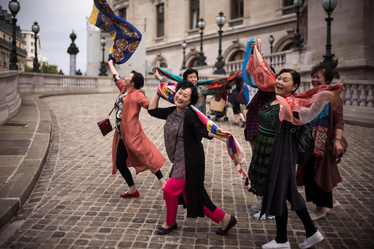 Image: Asian tourists pose for pictures in front of the Opera Garnier