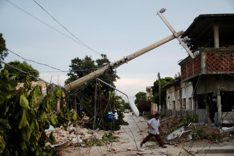 Image: A resident walks near earthquake debris in Juchitan, Mexico.