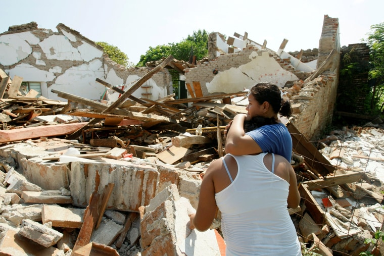 Image: Women hug while next to a destroyed house in Union Hidalgo, Mexico after the powerful earthquake.