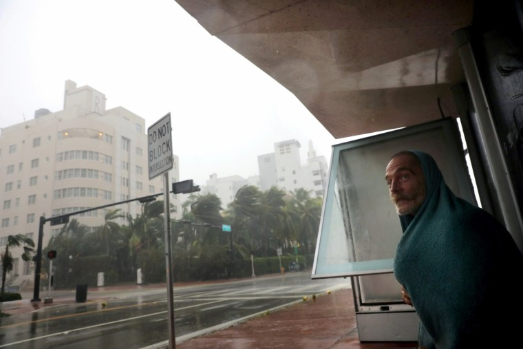 Image: A homeless man takes shelter at a bus stop in Miami Beach on Sept. 10.
