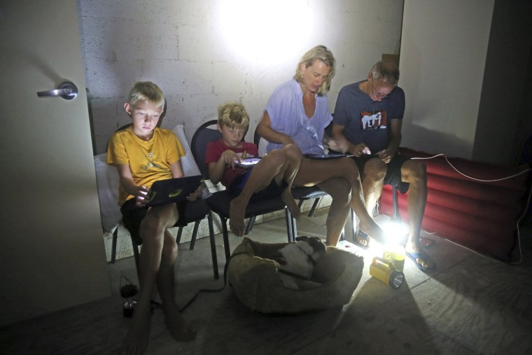 Image: The Blinckman family use their personal devices while sheltering in a stairwell utility closet as Hurricane Irma goes over Key West on Sept. 10.