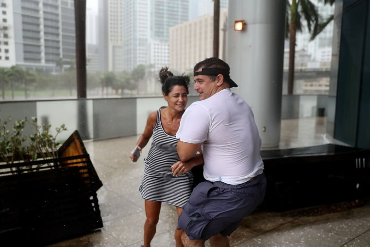 Image: People battle high winds and rain to take in the sights along the Miami River which is flooding as Hurricane Irma passes through on Sept.10.