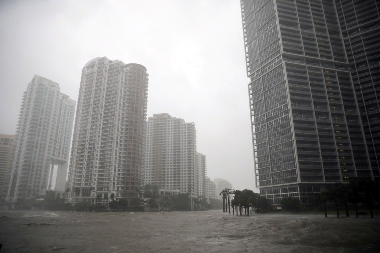 Image: Water rises up to a sidewalk by the Miami river in Downtown Miami on Sept. 10.