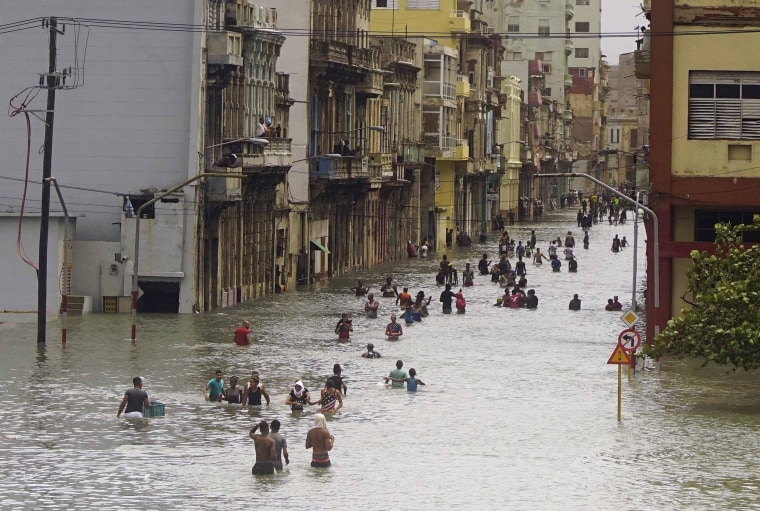 Image: People move through flooded streets in Havana after the passage of Hurricane Irma