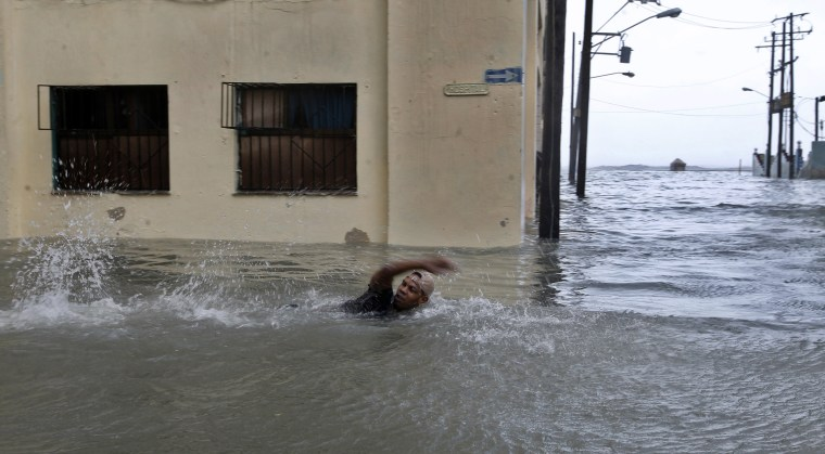 Image: A man swims on a flooded street in Havana
