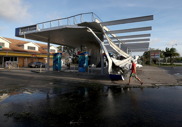 Image: A man looks at the damaged roof of a gas station that succumbed to Irma's winds in Bonita Springs on Sept. 11.