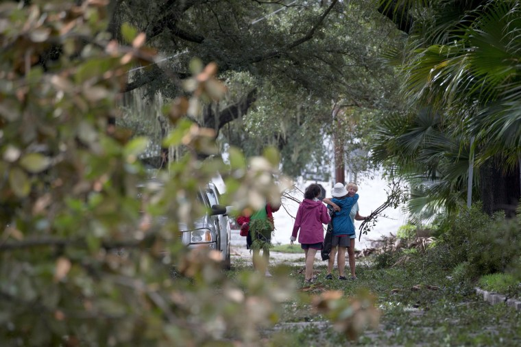 Image: Neighbors embrace while clearing fallen trees and brush outside their homes along Bayshore Blvd in Tampa on Sept. 11.