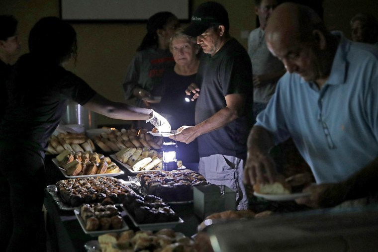 Image: Hotel guests are served breakfast by lamplight as the power remains off at the Courtyard by Marriott in Fort Lauderdale on Sept. 11.