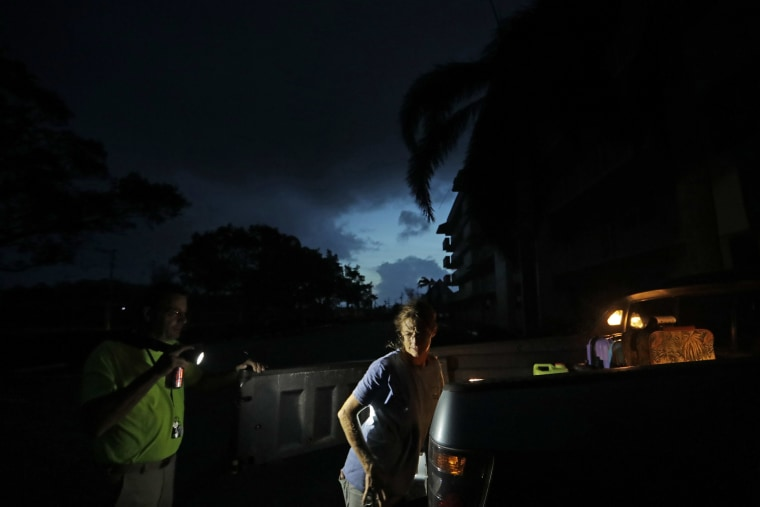 Image: Laura and Joe Raymond pack up their truck to leave the fourth floor apartment of Joe's mother, where they rode out the hurricane, to return to their low lying home a mile away in Marco Island on Sept. 11.