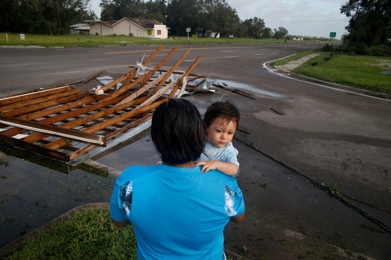 Image: Gonzalo Saldivar and his one year-old son Luke get their first look at the roof that flew off of their home and landed at a nearby intersection in Bowling Green on September 11.