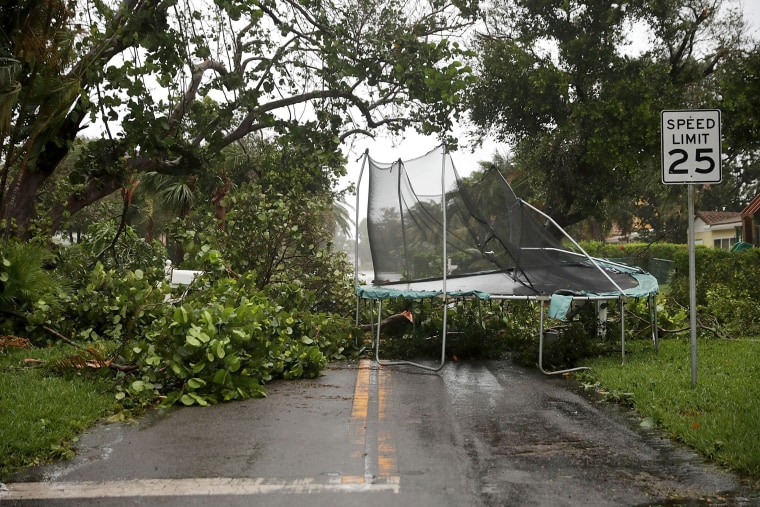 Image: Downed trees and a windblown trampoline block a street in Pompano Beach on Sept.10.