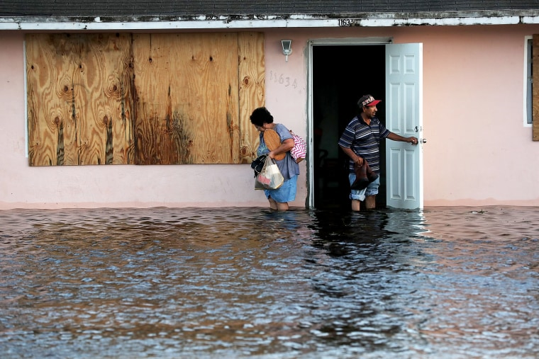 Image: A couple leave their flooded home in Fort Myers the morning after Hurricane Irma swept through the state on Sept. 11, 2017.
