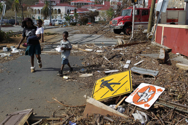 Image: A woman with her two children walk past debris left by Hurricane Irma in Charlotte Amalie, St. Thomas