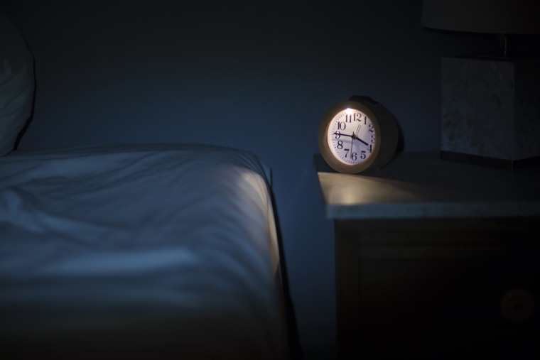 Image: An alarm clock sits on a bedside table