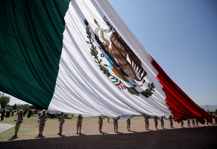 Image: Soldiers hold a giant national flag as it is raised during preparations for the 207th anniversary of Mexico's independence from Spain, to be celebrated on September 16, in Ciudad Juarez