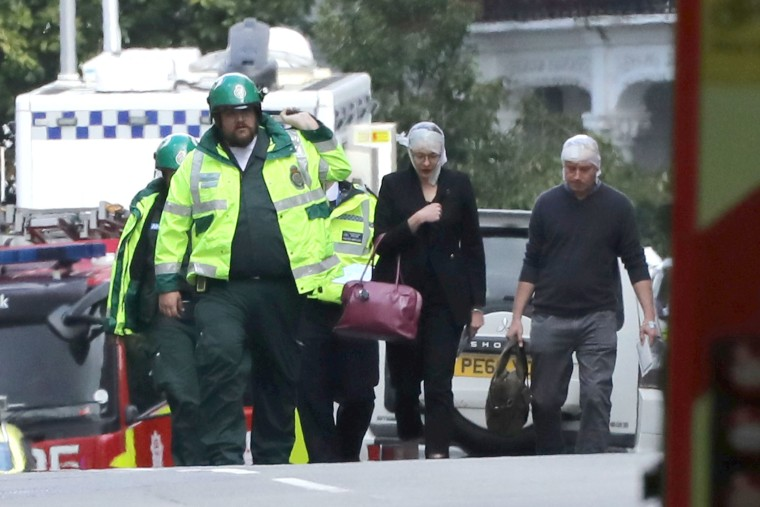 Image: An injured woman is led away after an incident at Parsons Green