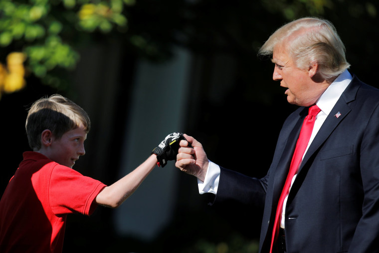 Image: U.S. President Donald Trump shakes hands with 11-years-old Frank Giaccio as he cuts the Rose Garden grass at the White House in Washington