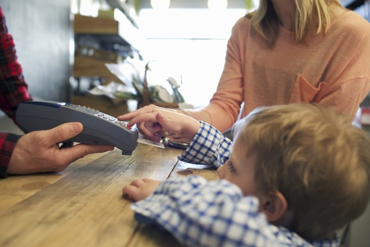 Image: A child uses a credit card machine