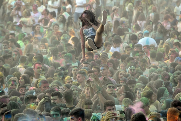 """Image: A participant is tossed in the air during the \""""Day of Colors\"""" in Thermi, Greece"""