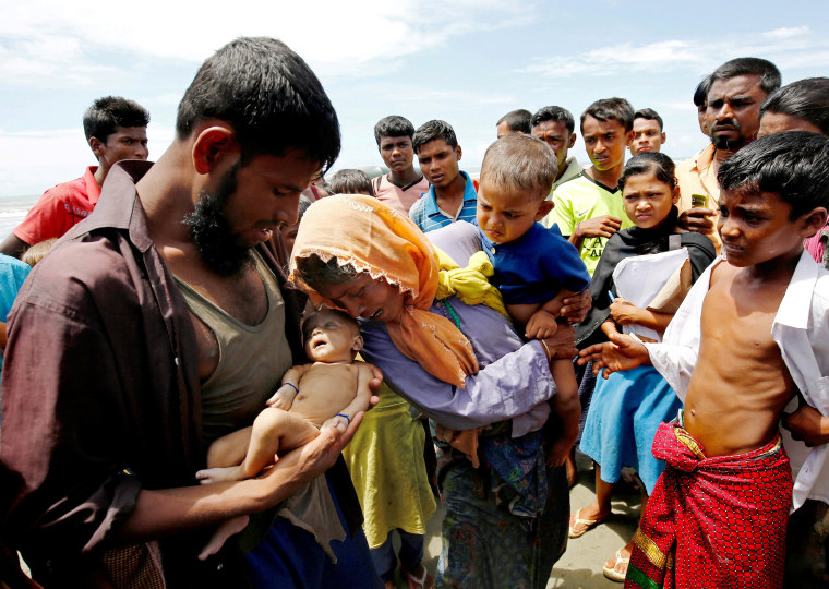 Image: Nasir Ahmed and his mother cry above Nasir's 40-day-old son who died as a boat capsized in the shore of Shah Porir Dwip while crossing Bangladesh-Myanmar border, in Teknaf