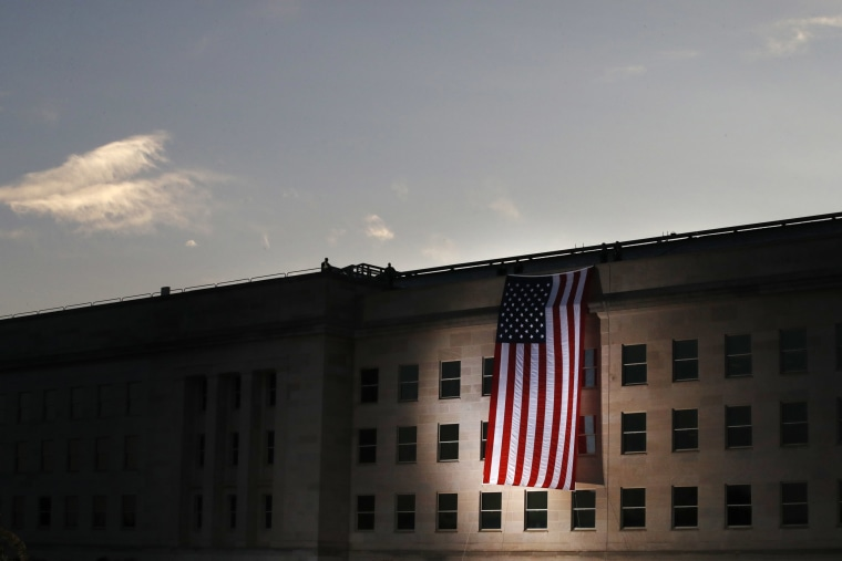 Image: A U.S. flag is unfurled at sunrise at the Pentagon