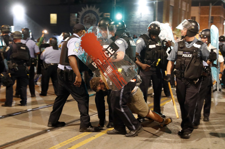 Image: Police arrest a man as they try to clear a violent crowd
