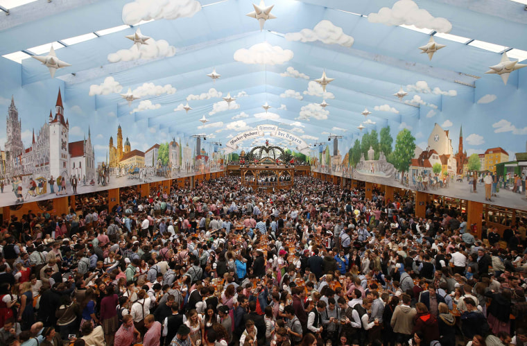 Image: Visitors gather in a tent during the opening day of the 184th Oktoberfest in Munich