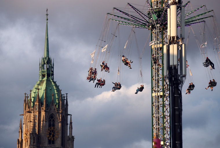 Image: Visitors ride a during the opening day of the 184th Oktoberfest in Munich