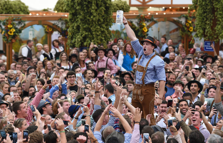 Image: People cheer as a man lifts his empty mug after finishing his beer