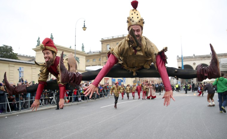 Image: Performers do splits in the air during the Oktoberfest parade in Munich