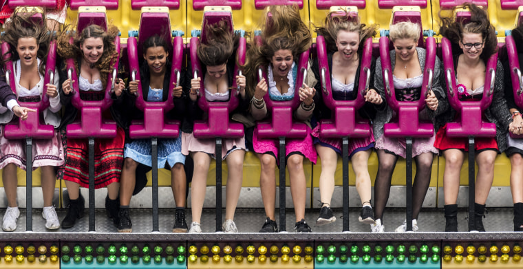 Image: Visitors scream during a ride at the fairground