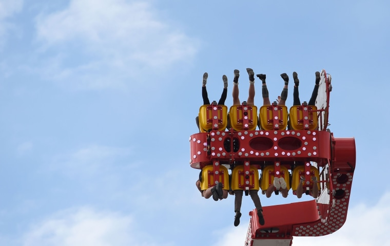 Image: People sit in a fairground ride at the 184th Oktoberfes