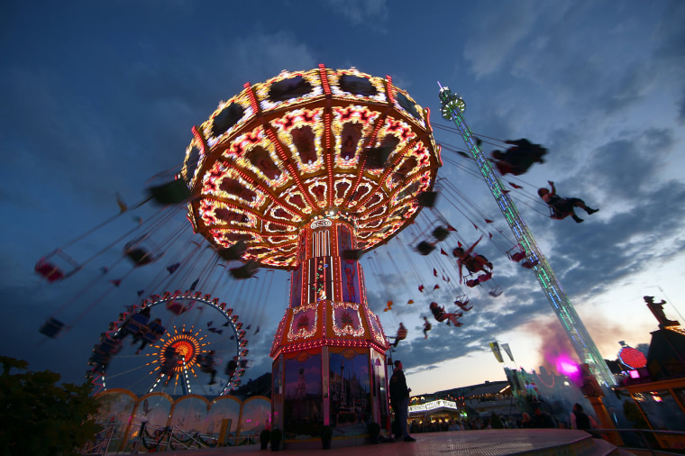 Image: People ride a swing ride during the opening day of the 184th Oktoberfest in Munich