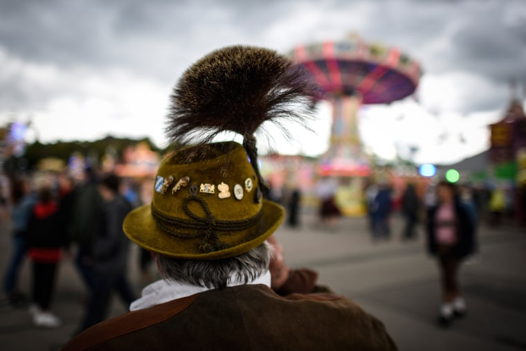 Image:  A reveler in traditional bavarian clothes stands in fron of a caroussel on the first day of the 2017 Oktoberfest beer fest