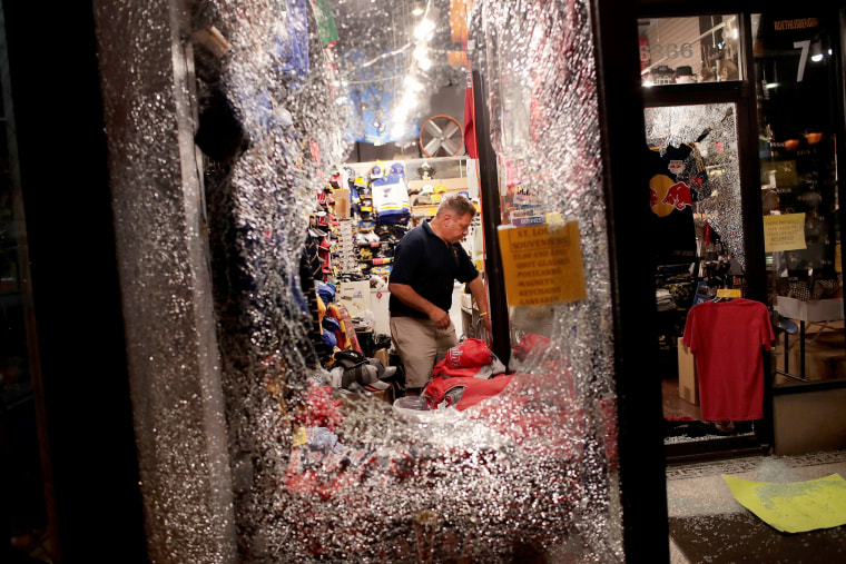 Image: A worker cleans up broken glass from a window smashed during the protest.