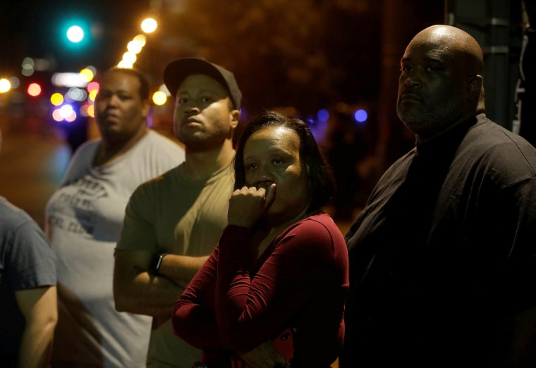 Image: Bystanders watch police officers in riot gear and demonstrators as they continue to protest.